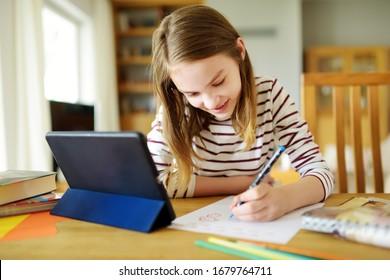 Preteen schoolgirl, die ihre Hausaufgaben mit digitalen Tablets zu Hause macht. Kind, das Gadgets zum Lernen benutzt. Bildung und Fernunterricht für Kinder. Unterricht während der Quarantäne. Bleiben Sie zu Hause Unterhaltung.
