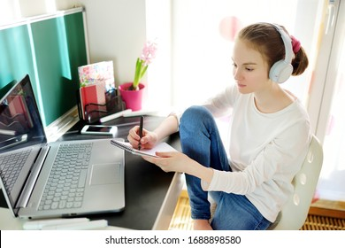 Preteen schoolgirl doing her homework with laptop computer at home. Child using gadgets to study. Online education and distance learning for kids. Homeschooling during quarantine. Stay at home.