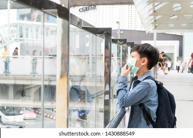 A preteen / teenage asian boy standing on skywalk in city center wearing medical mask to protect from Virus, Air pollution, PM 2.5, Epidemic, Hazardous particles. Health care in big city concept.