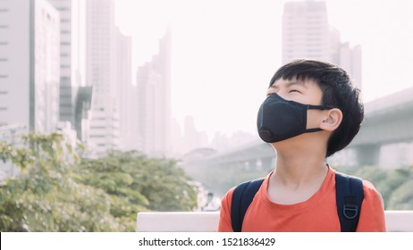 A preteen/teenager asian boy standing on skywalk in a big city wearing filtering dust mask to protect himself from PM 2.5, Air pollution, Pollen, Virus, Hazardous particles. Poor air quality, AQI