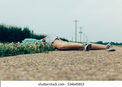 The pretend dead body series. Woman pretending she is dead on the side of the gravel road in the state of Mississippi. Woman wearing shorts and sneakers.