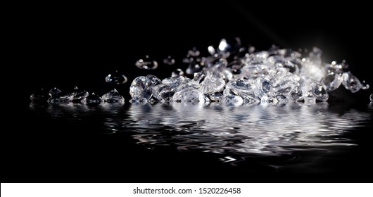 Pretend diamonds in a pile next to water with a reflection, all on a black background