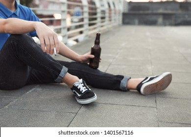 Pretending to be cool. Teen guy smoking cigarette and drinking beer, sitting on roof alone, empty space