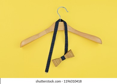 Pre-tied bow hanged into wooden hanger on yellow background. Preparing for party, date, corporate dinner concept