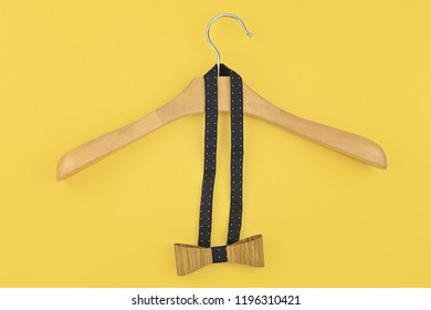 Pre-tied bow hanged into wooden hanger on yellow background. Preparing for party, date, corporate Christmas dinner concept