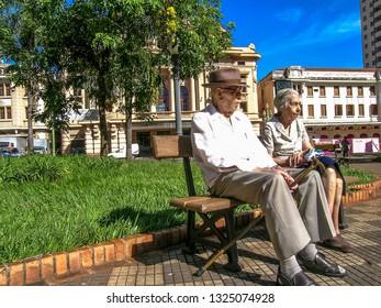 Ribeirão Preto, SP, Brasil, 13/02/2004. Casal de idosos sentado em um banco na Praça XV de Novembro, centro de Ribeirão Preto, SP.