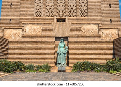 PRETORIA, SOUTH AFRICA, JULY 31, 2018: The bronze sculpture of a Voortrekker woman and two children at the Voortrekker Monument  in Pretoria. Four relief panels of a black wildebeest are visible