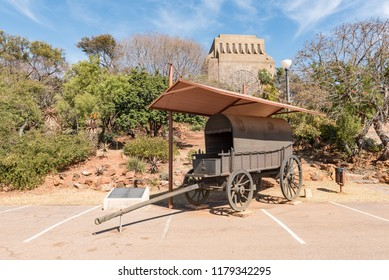 PRETORIA, SOUTH AFRICA, JULY 31, 2018: A bronze replica of a jawbone wagon with the Voortrekker Monument in Pretoria in the back