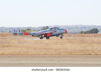 PRETORIA, SOUTH AFRICA-JULY 2 2016: de Havilland Vampire in training colors landing with smoke from its tyres at the Swartkops Museum Flying Day