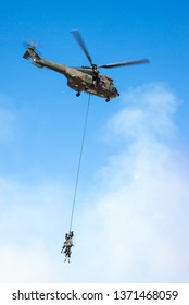 PRETORIA, SOUTH AFRICA-MAY 5 2018: SAAF museum Puma helicopter hoists 5 troops on a wire rope in full kit during mini air war at the Swartkops Museum Airshow