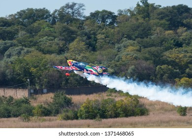 PRETORIA, SOUTH AFRICA-MAY 5 2018: Partrick Davidson in a Red Bull Racing Sback flies towards the boundry fence with smoke on at the Swartkops Museum Airshow