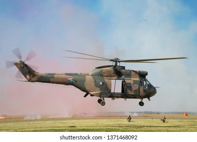 PRETORIA, SOUTH AFRICA-MAY 5 2018: SAAF museum Puma helicopter demonstrates operational take off with red marking smoke during mini air war at the Swartkops Museum Airshow