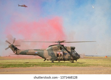 PRETORIA, SOUTH AFRICA-MAY 5 2018: SAAF museum Puma helicopter landing with red smoke and grass  during mini air war at the Swartkops Museum Airshow