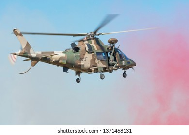 PRETORIA, SOUTH AFRICA-MAY 5 2018: SAAF Augusta  A109 helicopter with red marking smoke hovering during mini air war at the Swartkops Museum Airshow