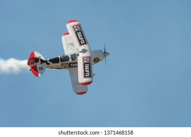 PRETORIA, SOUTH AFRICA-MAY 5 2018: An aircraft from the COWS Tailifts sponsored Pitts Special team banks towards crowd line at the Swartkops Museum Airshow