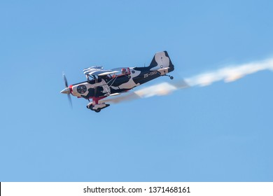PRETORIA, SOUTH AFRICA-MAY 5 2018: An aircraft from the COWS Tailifts sponsored Pitts Special team with smoke on at the Swartkops Museum Airshow