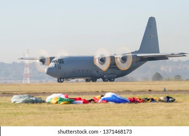 PRETORIA, SOUTH AFRICA-MAY 5 2018: A C130 transport aircraft lands with colourful parachutes in foreground at the Swartkops Museum Airshow