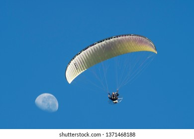 PRETORIA, SOUTH AFRICA-MAY 5 2018: A powered paraglider flies with the moon in the background at the Swartkops Museum Airshow