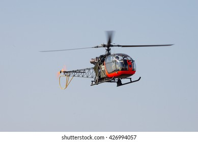 PRETORIA, SOUTH AFRICA-MAY 7 2016: An Alouette II helicopter with dayglo finish hovers at the Swartkops Museum Airshow
