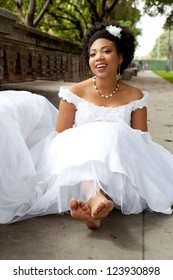 Pretty African American Bride is smiling sitting on the ground with Barefett