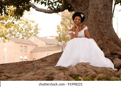 Pretty African American Bride is smiling at you in the park