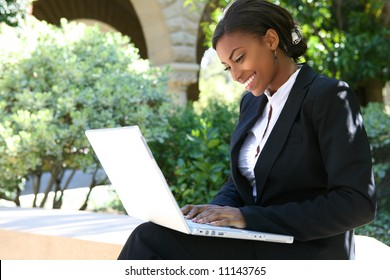 A pretty african american business woman at college on computer