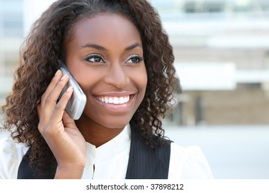 A pretty African american business woman talking on a  cell phone at office building