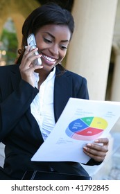 Pretty African American Business Woman on the Phone Holding Report