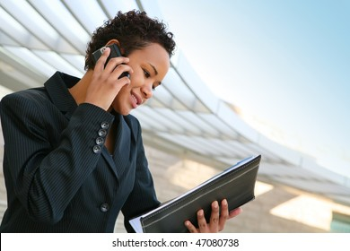 A pretty african american business woman at her company on the phone