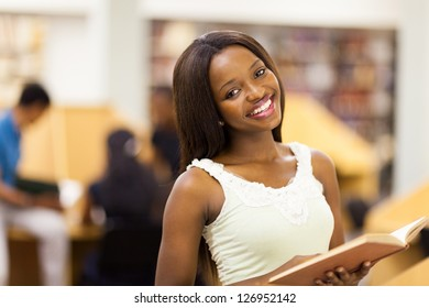 pretty african american college student reading in library
