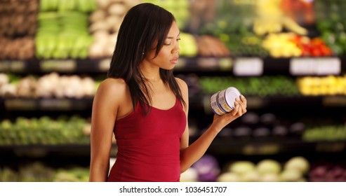 Pretty African American female examining tuna can at supermarket