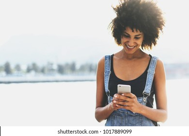 Pretty African American girl holding a smartphone in the rays of the evening sun. Beautiful smiley girl reads incoming e-mails via modern cellphone using 3g internet on a sea background