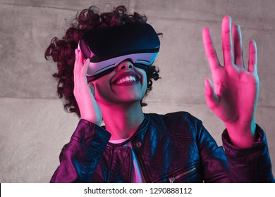 Pretty African American teenager smiling and waving hand while standing near concrete wall exploring virtual reality