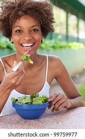 pretty African American woman with a healthy salad in a park
