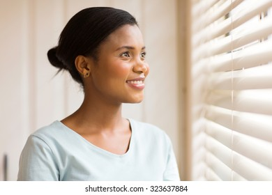 pretty african american woman looking through the blinds