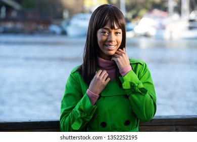 Pretty African American woman near a body of water wearing vibrant green jacket