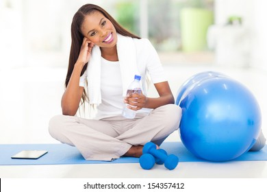 pretty african american woman resting at gym
