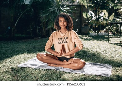 """Pretty african american woman sitting on green grass doing yoga. T-shirt with sign """"follow your karma"""". Phuket. Thailand."""