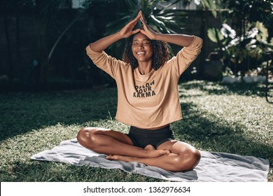 "Pretty african american woman sitting on green grass doing yoga. T-shirt with sign ""follow your karma"". Phuket. Thailand."
