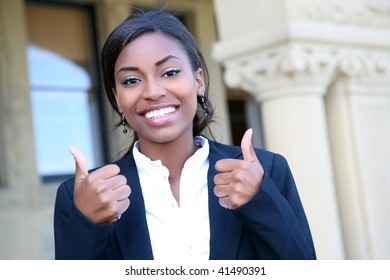 A pretty african american woman student at college with thumbs up