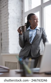 Pretty african businesswoman standing near window and drinking coffee or tea while resting and thinking about something