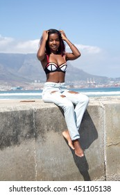 A pretty african female in jeans and a bikini top sitting on a cement pier by the beach