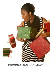 Pretty african girl holding her christmas presents and dropping two