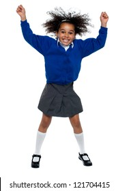 Pretty African school girl dances in full swing. Isolated over white background.