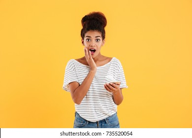 Pretty african surprised lady looking camera while using smartphone isolated over yellow