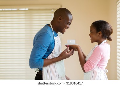 pretty african woman giving coffee to her husband at home