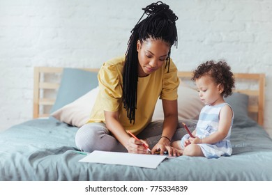 Pretty African woman sitting on bed with her baby daughter and drawing on paper with crayons.
