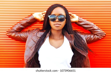 Pretty african woman in sunglasses and jacket at city over red background