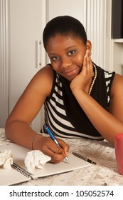 Pretty african woman writing a letter at home