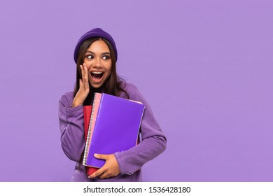 Pretty african-american teenager in a hat and sweater holding folders and expressing emotion of surprise standing isolated over purple background. Concept of education
